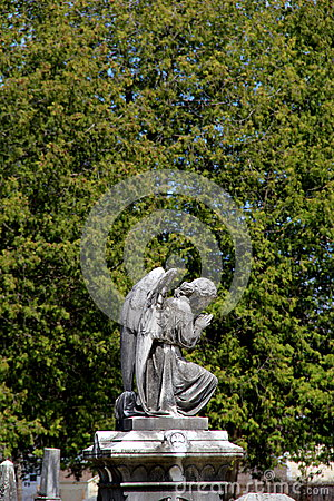 Old stone statue of angel praying in cemetery Stock Photo