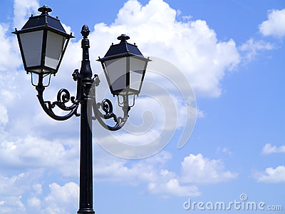 Old street decorated lamppost against cloudy blue sky