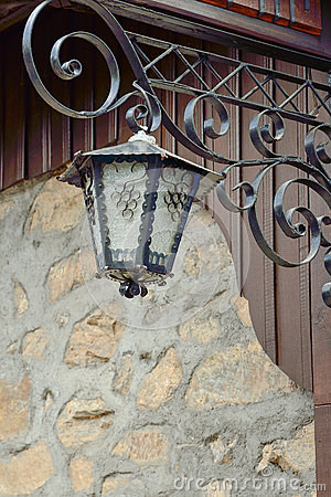 An old street lamp on a stone wall