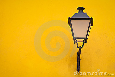 Old street lamp on a yellow wall