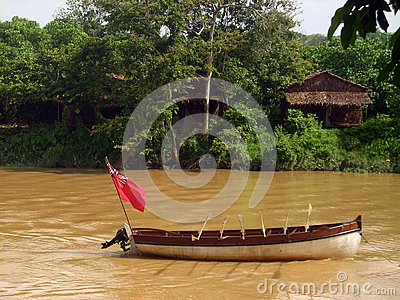 Old style boat with flag at muddy river