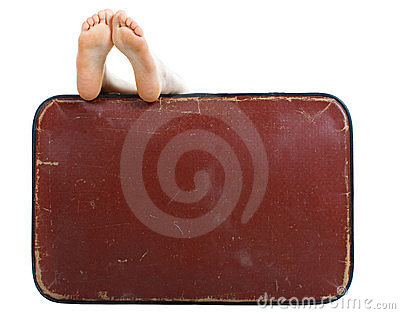 Old suitcase with naked female feet on top