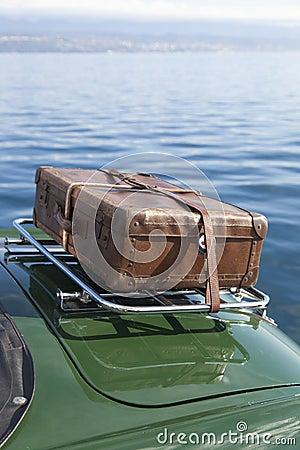 Old suitcase on vintage sport car