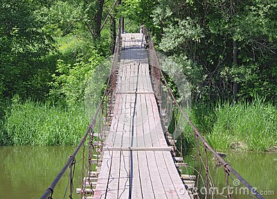 Old suspension walk bridge across river in forest