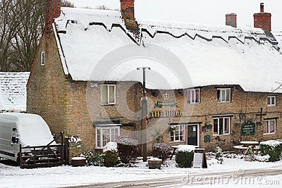 Old thatched public house in the snow. Editorial Stock Photo