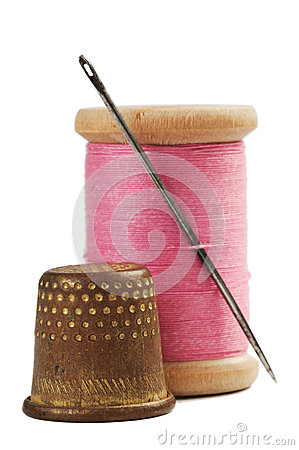 Old thimble and needle with pink thread