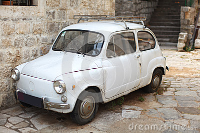 Old-timer white small italian car parked in an all