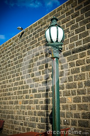 Free Old Town Street Lamp Post With Wall And Blue Sky Royalty Free Stock Image - 26518306