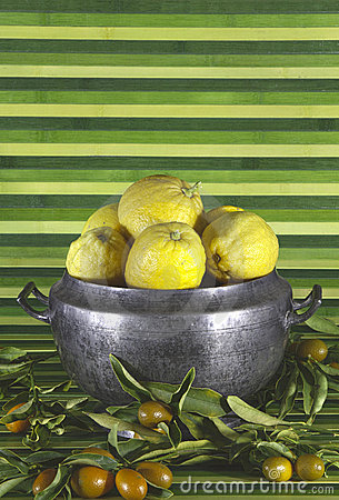 Old tureen with lemons,mandarins,green background