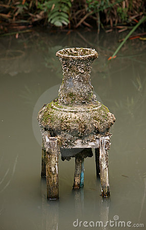 Old vase-fountain on pond in Thailand