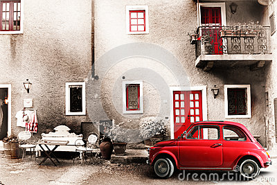 Old vintage italian scene. Small antique red car. Aging effect