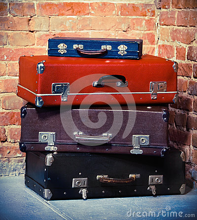 Old vintage suitcases isolated near brick wall