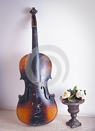 Old violin leaning against the wall near a flower vase with roses
