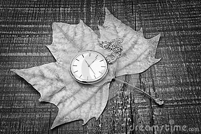 Old watch on the autumn leaf. The symbol of nostalgia.
