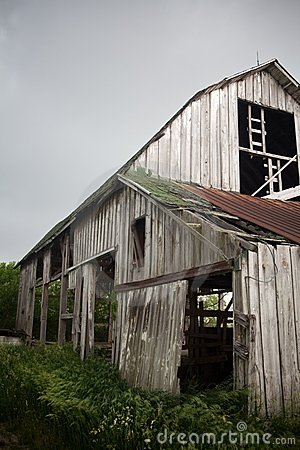 Old, Weathered Barn with Rusty Roof Lashed by Wind