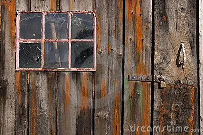 Old weathered and worn wooden planks with door and pink framed window