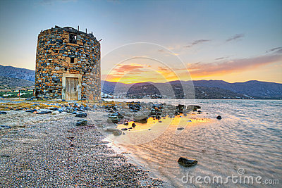 Old windmill ruin on Crete at sunset