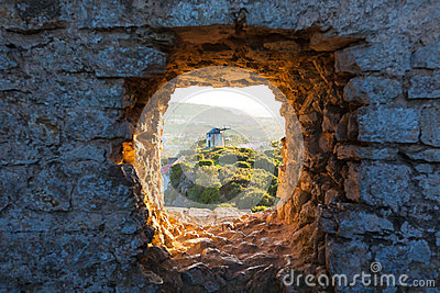Old Windmill through Window in Fortress Wall