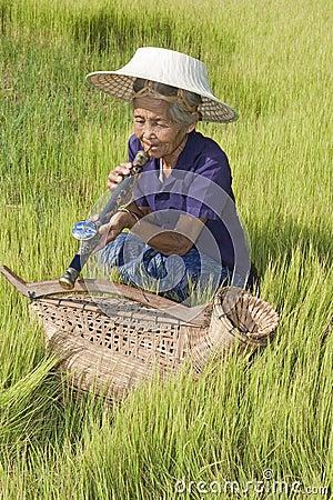 Old woman Asia smoking opium pipe