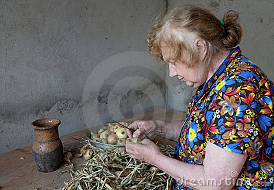 The old woman cuts an onions at itself