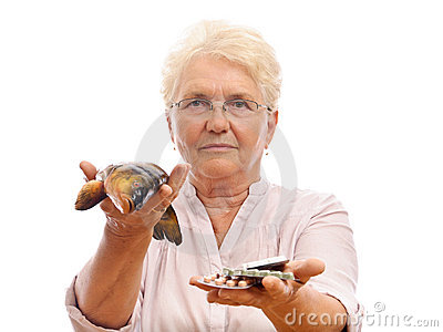 Old woman with fish and pills in balance