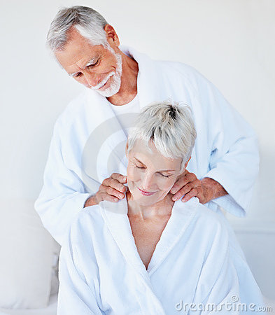 Old woman getting a massage from loving husband