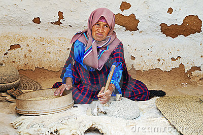 Old woman grinds grains Editorial Photography