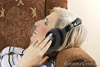 Old woman with headphones in sofa