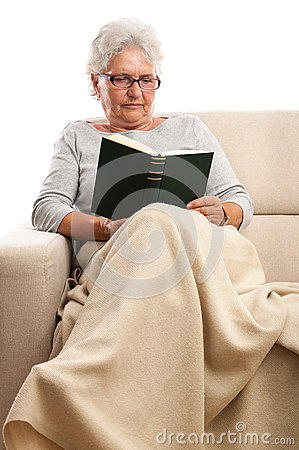 Old woman at home reading book