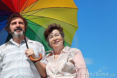 Old woman and man holding multicolored umbrella