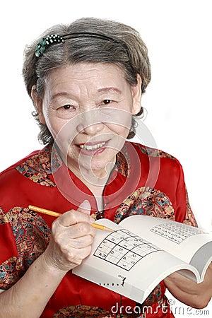 Old woman play sudoku