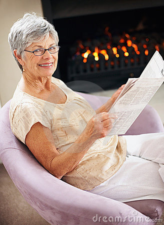 Old woman reading a newspaper by the fireplace