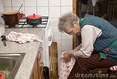 Old woman by rest in kitchen
