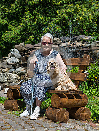 Old woman sitting on a bench with a dog