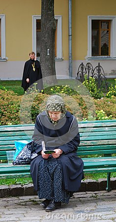 Old woman sitting on a bench reading a book Editorial Stock Image