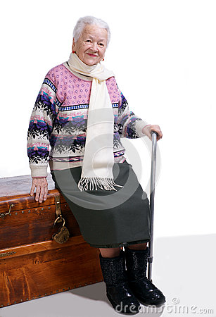 Old woman sitting on a box with a cane