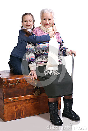 Old woman sitting on a box with her granddaughter