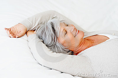 Old woman sleeping in bed with a smile on her face