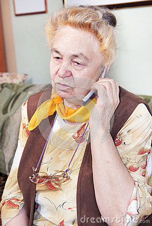 Old woman is speaking by a mobile
