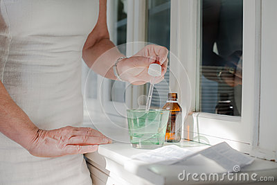 Old woman taking prescription drugs and drinking