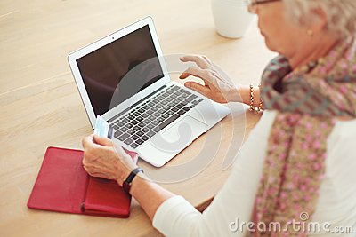 Old Woman Using Laptop with Blank Screen