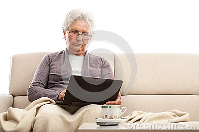 Old woman using tablet with keyboard dock at home