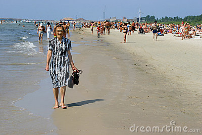 Old woman walking and relaxing in Crowded beach Editorial Stock Image