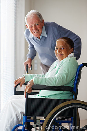 Old woman on a wheel chair , husband at the back