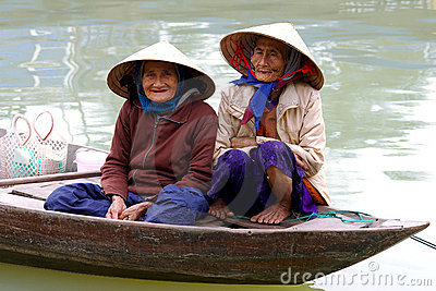Old womans in a boat on a street in Hoi An, Vietna Editorial Stock Image