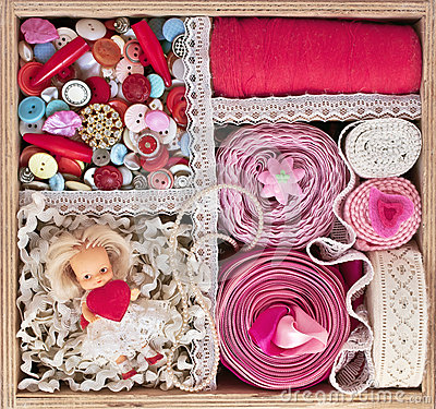 Old wooden box with thread, buttons and ribbons