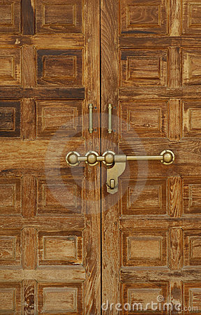 Old wooden door with a massive brass lock, India