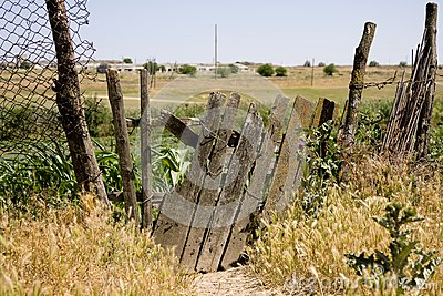 Old wooden fence on the thrown farm