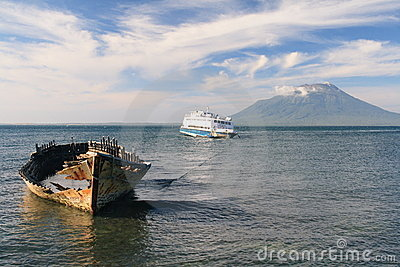 Old wooden ferry in front of a volcano, Indonesia