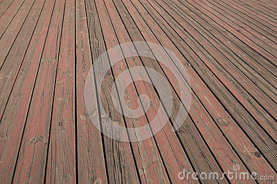 Old wooden floor texture, battered strip wooden board flooring, grain of wood floorboard with peeled off red paint